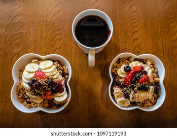 Healthy Acai berry bowls with fruit and granola and black coffee.