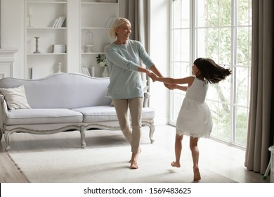 Healthy active 50s grandmother holding hands little granddaughter dancing or spinning standing barefoot in modern warm living room enjoy priceless time together at funny weekend activities concept