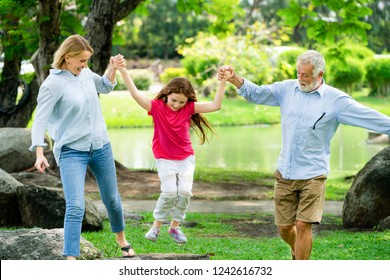Healthy active father and mother in the park grabbing and playing with daughter child on weekend in summer. Active senior and family lifestyle concept.