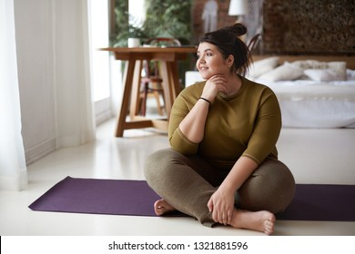 Healthy active lifestyle, fitness, pilates, dieting and excess weight concept. Charming barefooted plus size young woman in sportswear sitting cross legged on mat, going to practice yoga, smiling