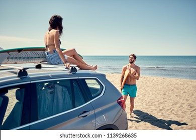Healthy Active Lifestyle. Surfing. Summer Vacation. Extreme Sport. Smiling surfer girl sitting on the car and getting ready for surfing