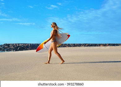 Healthy Active Lifestyle. Surfing. Water Sports. Beautiful Athletic Surfer Woman With Sexy Fit Body In Bikini With Surf Board Walking On Sea Beach. Summer Vacation. Extreme Sport. Summertime Fun Hobby