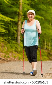 Healthy active retirement concept. Senior woman practicing nordic walking in forest park. Elderly female enjoying nature fresh air