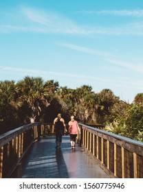 Healthy active women walk the boardwalk at New Smyrna Dunes Park in New Smyrna Beach, Florida