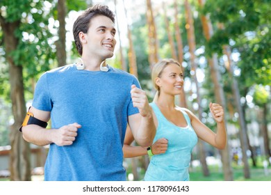 Healthy activity. Delighted nice woman smiling while running together with her boyfriend