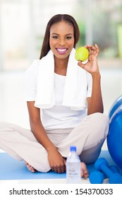 healthy african american woman holding apple after working out