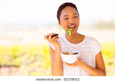 healthy african woman eating vegetable salad at home