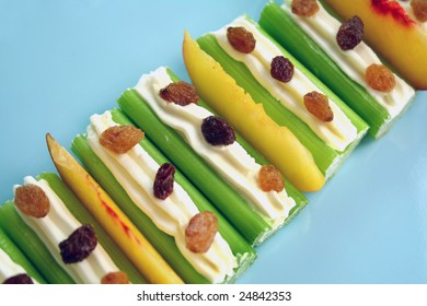 Healthy afternoon snack of celery sticks with cream cheese and sultanas.