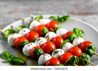 Healthy appetizer - caprese salad with tomato and mozzarella, italian food of mediterranean diet with olive oil dressing, weight loss concept
