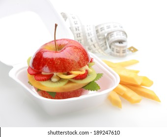 Healthy apple burger takeaway in a fast food container with a juicy red apple sliced through and filled with diced fresh tropical fruit and sauce with fruit batons or chips and a tape measure