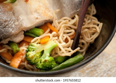 Healthy Asian fish and vegetable noodles in a close up view with broccoli and carrots served in a black bowl