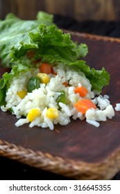 Healthy Asian food, rice wrapped in lettuce leaves. Rice cooked with corn, bean and carrot.
