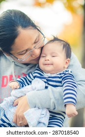 Healthy Asian mother wearing sweater (tracksuit) cuddles and kisses her 2 month old newborn baby boy after exercise