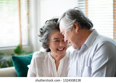 Healthy Asian older people laughing and relaxing at their house together. Happy smiling Elderly man and woman celebrating Anniversary. Joyful senior couple in love. Copy space.