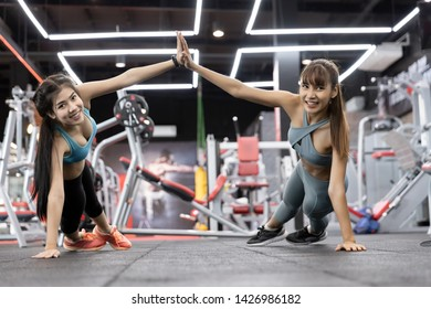 Healthy asian two people young woman Push-up on weights and giving high five to each other while working out together at gym