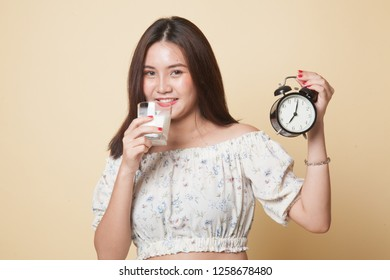 Healthy Asian woman drinking  glass of milk hold clock on beige background