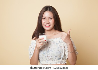 Healthy Asian woman drinking a glass of milk thumbs up on beige background