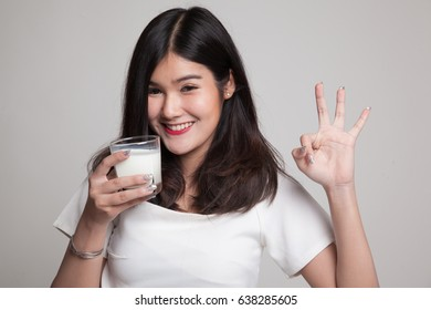 Healthy Asian woman drinking a glass of milk show OK sign on gray background
