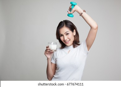 Healthy Asian woman drinking a glass of milk and dumbbell on gray background