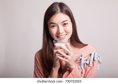 Healthy Asian woman drinking a glass of milk on gray background