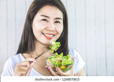 healthy Asian woman eating salad for diet and smiling to the camera