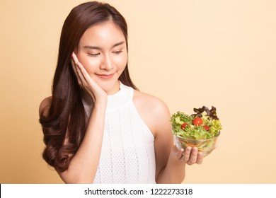 Healthy Asian woman with salad   on beige background.