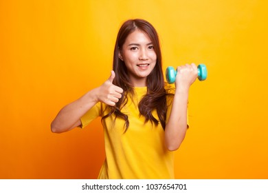Healthy Asian woman thumbs up with dumbbells in yellow dess on yellow background