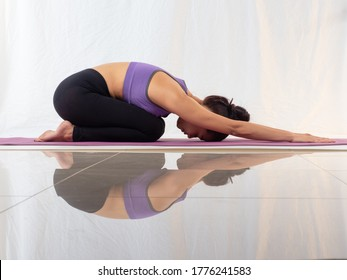 Healthy Asian woman wearing sportswear practicing yoga, Child's pose on white background wiht reflection on the floor. - Shutterstock ID 1776241583