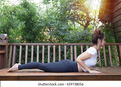 Healthy Asian Women Relaxing In Yoga Baby Cobra Pose On Wooden Terrace With  Warm Light Effect