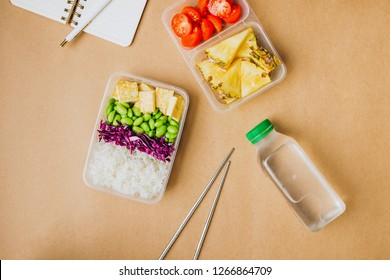 Healthy asian-style vegan bento box with rice, fried tofu, edamame beans and cherry tomatoes and pieces of pineapple with metal chopsticks on side, flatlay