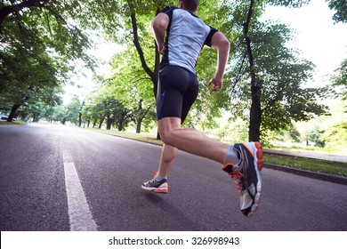 healthy athlete man jogging at morning on empty  roat in the city