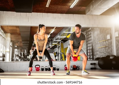 Healthy athletes exercise with kettlebells at fitness studio.