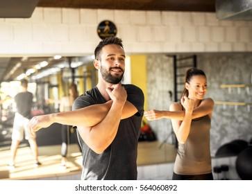 Healthy athletes exercising at gym.