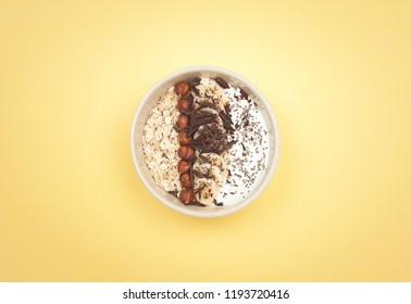 Healthy autumn breakfast. Energy bowl full of yoghurt, sliced banana, oatmeal, hazelnuts, chocolate and chia seeds on yellow background