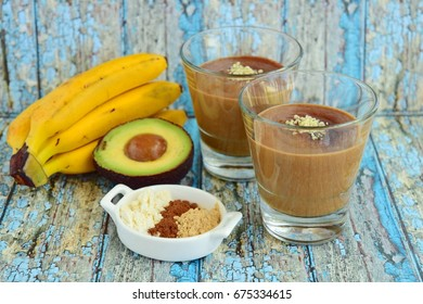Healthy avocado banana smoothie with cacao powder, whey protein, maca powder and hemp seeds on blue wooden background