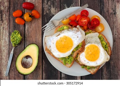 Healthy avocado, egg open sandwiches on a plate with cherry tomatoes on a rustic wood background