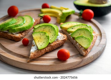 Healthy avocado toast with soft cheese, sliced avocado, cherry tomatoes and pepper on whole grain bread. Healthy nutrition, keto diet or easy recipe of vegaterian sandwich for vegan menu.