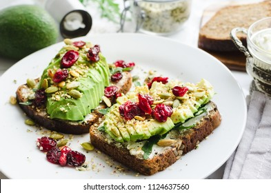 Healthy avocado toasts for breakfast or lunch with rye bread, cream cheese, arugula, sliced avocado, dried cranberry, pumpkin, hemp, sesame seeds, salt and pepper. Vegetarian sandwiches. Clean eating.
