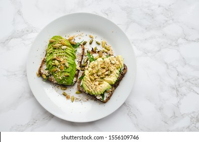 Healthy avocado toasts for breakfast or lunch with rye bread, sliced avocado, arugula, pumpkin and sesame seeds, salt and pepper. Vegetarian food. Plant-based diet. Clean eating. Top view. Copy space.