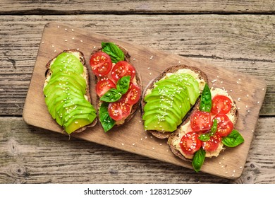healthy avocado toasts with avocado, cherry tomatoes, basil and sesame seeds on wooden cutting board. top view