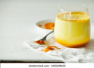 Healthy ayurvedic drink golden almond milk or pumpkin turmeric latte with curcuma powder on white background close-up copy space.Trendy Asian natural detox beverage with spices for vegans