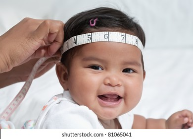 Healthy baby getting her head circumference measured, routine doctor checkup