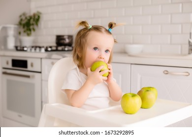 healthy baby girl sitting in a child's chair in the kitchen there are green apples