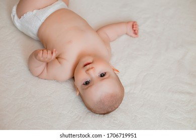 Healthy baby girl smiles lying on bed at home