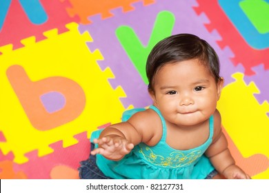 Healthy baby sitting in a colorful play mat