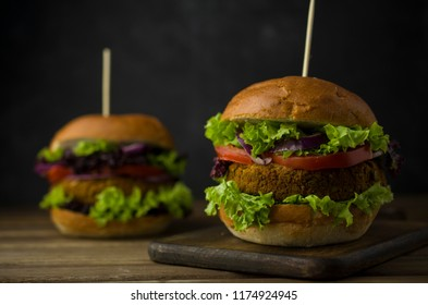 Healthy baked burger with whole grain bun and vegetables on a black board. Vegetarian food concept..