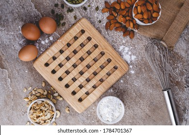 Healthy baking ingredients - flour, almond nuts,  eggs, over a stone table background. Bakery background frame. Top view, copy space.