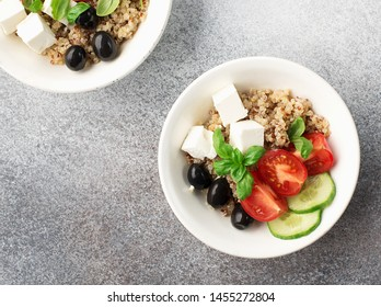 Healthy balanced appetizing salad bowl with quinoa, cucumber, tomatoes, feta cheese, olives, basil leaves on a gray background in a white plate. Top view