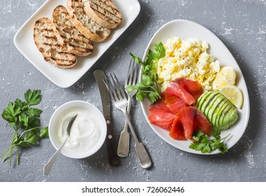 Healthy balanced breakfast or snack - smoked salmon, egg salad and avocado. On a gray background, top view. Healthy food concept