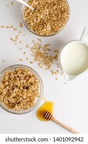 Healthy balanced eating concept. Proper nutrition menu for breakfast. Oatmeal porridge, milk and honey on white background. Vertical. Overhead shot.